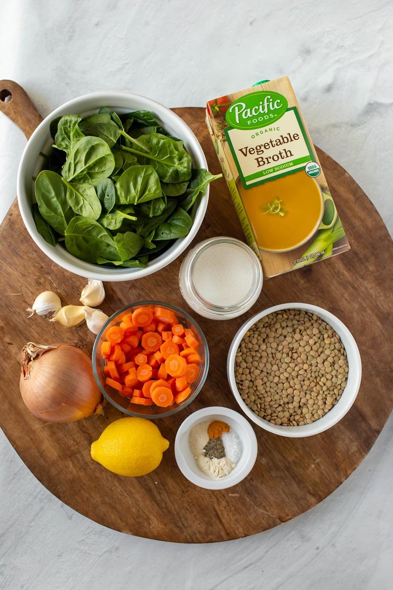 individual ingredients for vegan lentil soup on wood platter