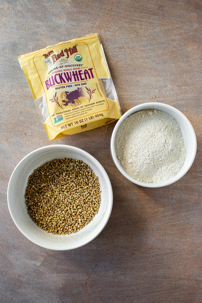 buckwheat groats in bowl next to buckwheat flour and bag