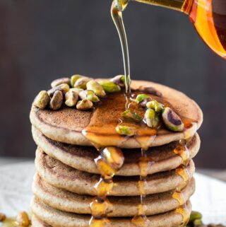 pouring maple syrup over stack of pancakes
