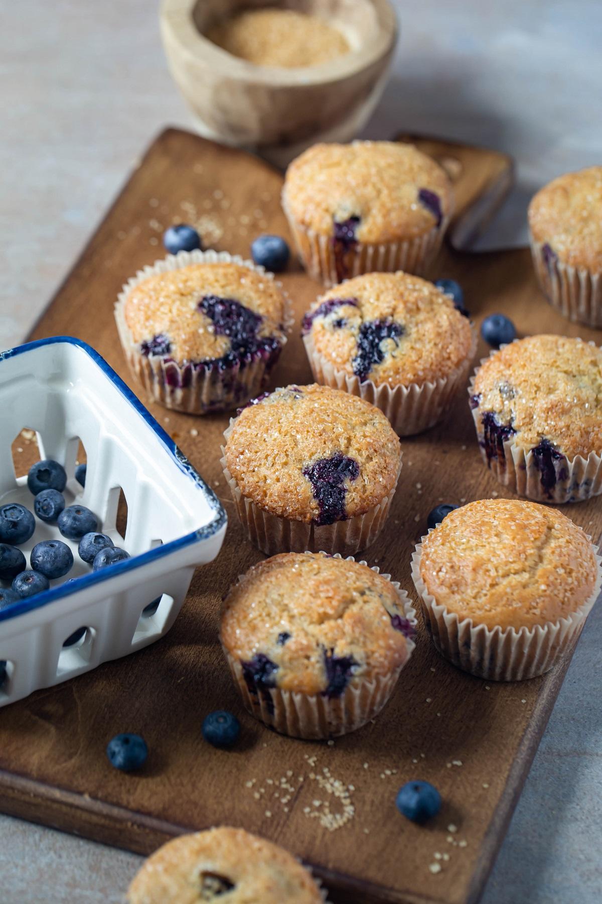 several vegan blueberry muffins on wood platter