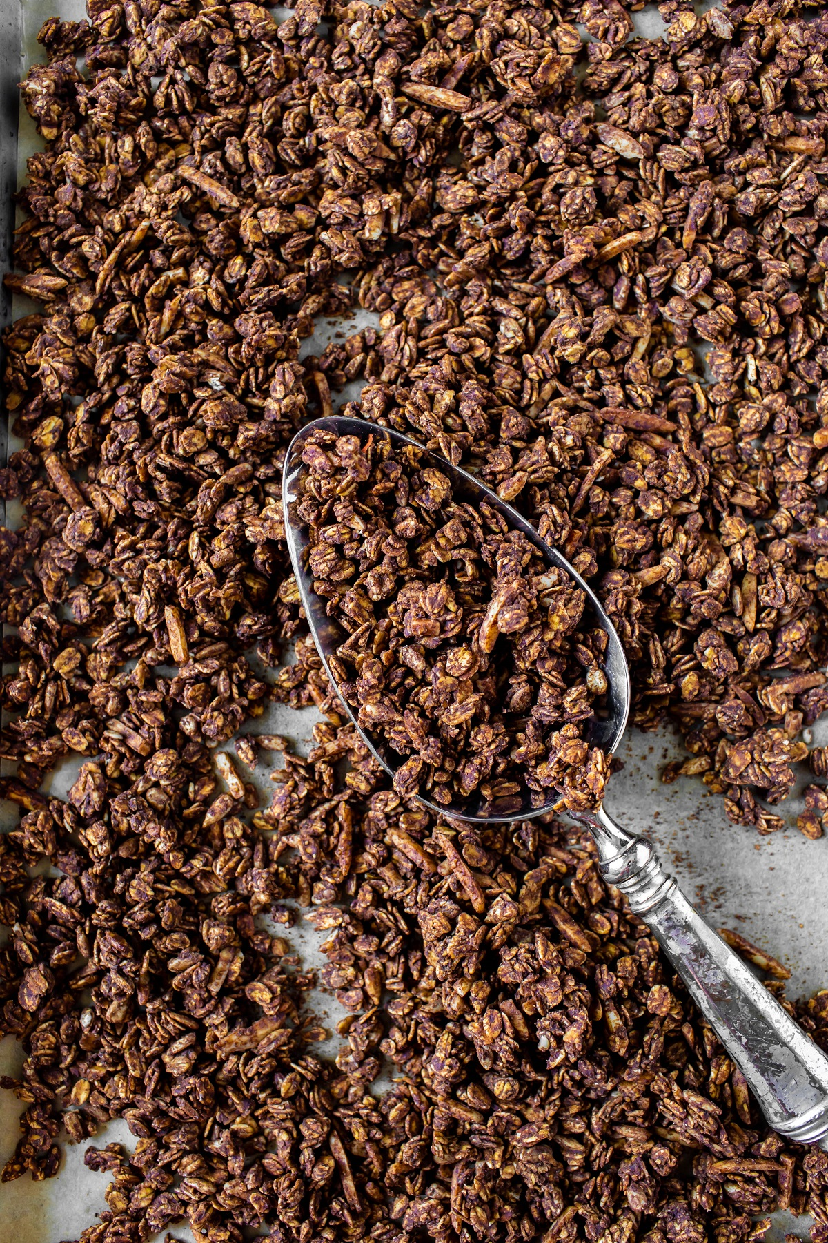 baked healthy chocolate granola with large spoon on tray