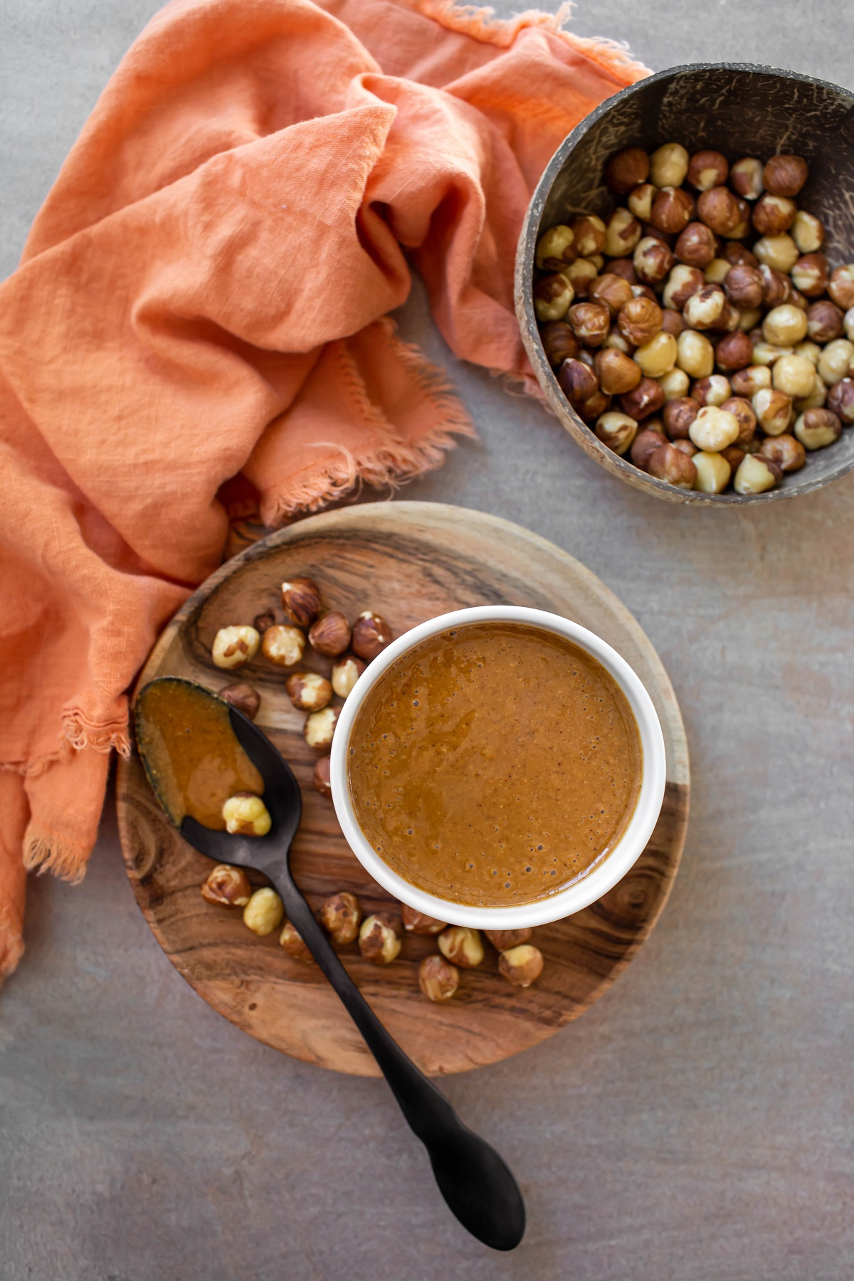 overhead shot of wood plate of hazelnuts with bowl of hazelnut butter and orange towel on side