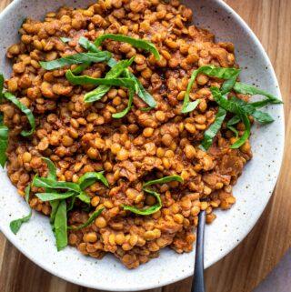 smoky vegan instant pot lentils in white bowl on wood platter