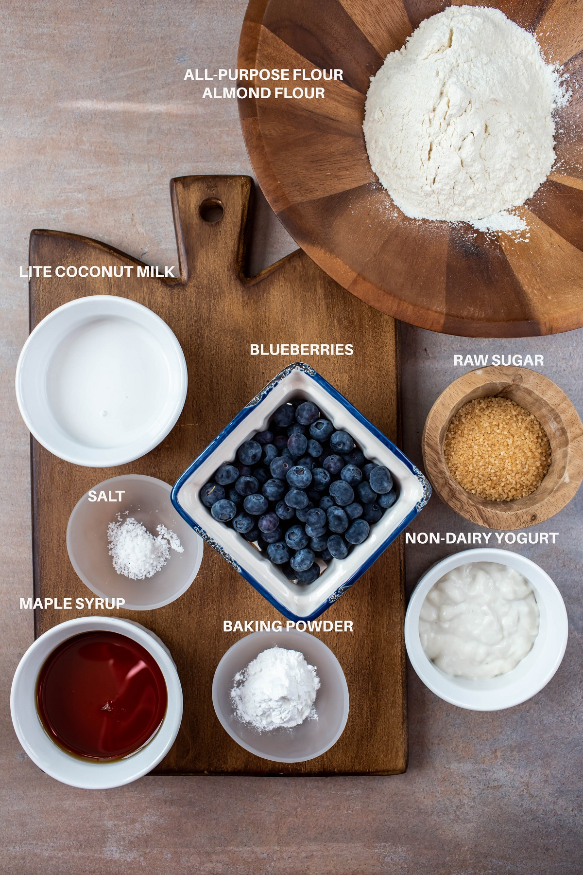 ingredients for vegan blueberry muffins in individual bowls on wood platter