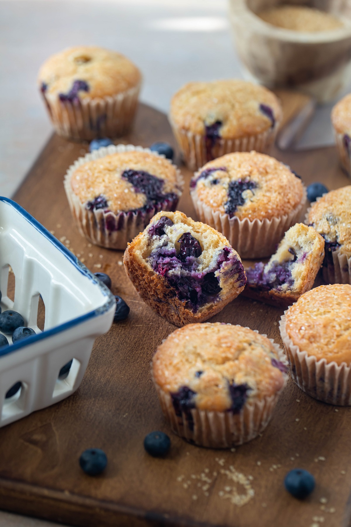 several blueberry muffins on wood platter with one open