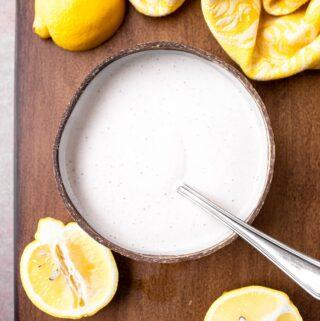 overheat shot of wood bowl of lemon sauce with fresh lemons and yellow towel