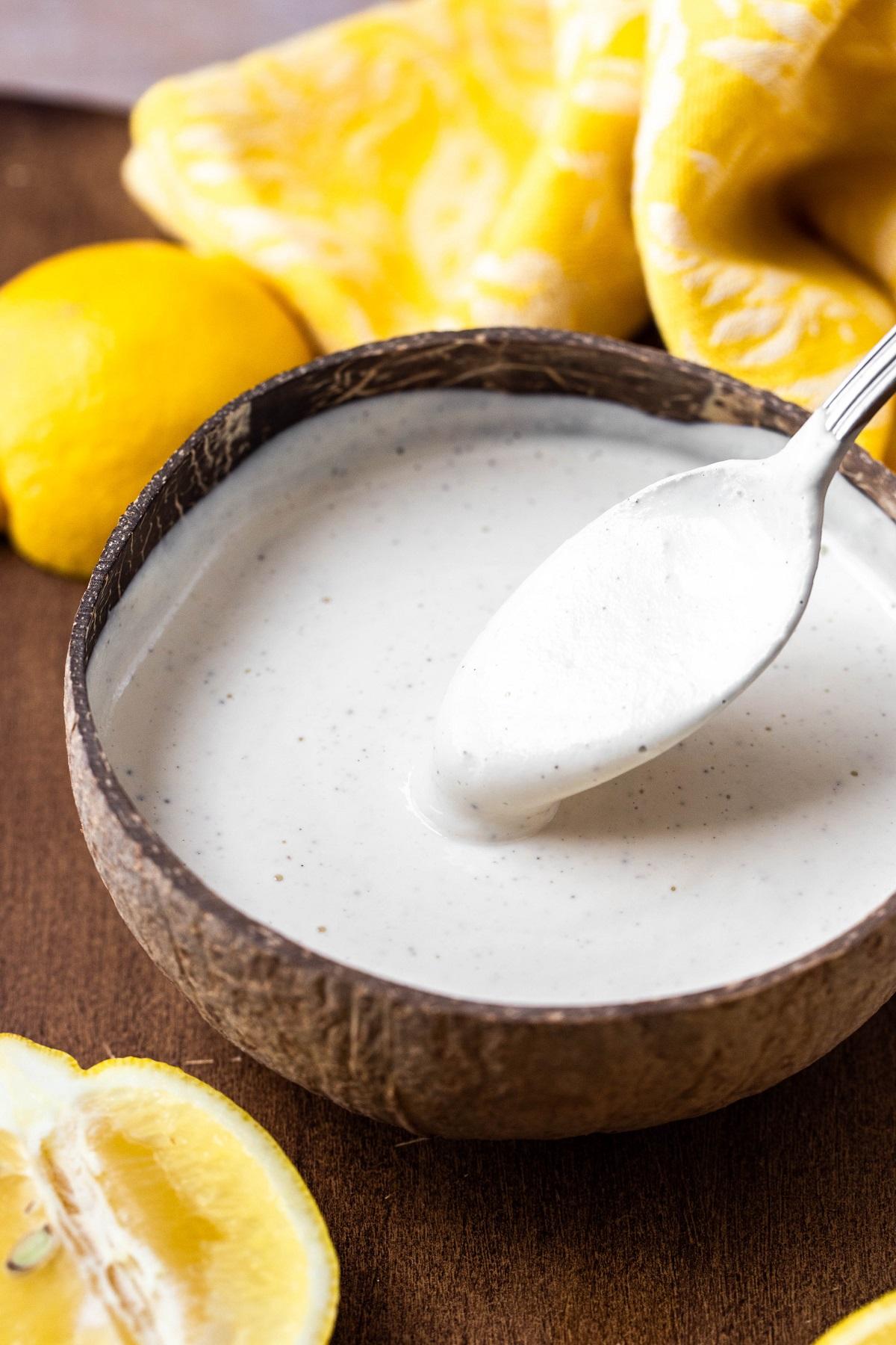 spoon dipping in wood bowl of vegan lemon sauce