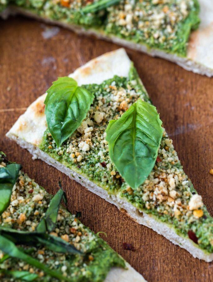 closeup of vegan pesto flatbread pizza slice on wood board