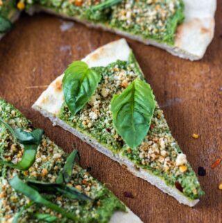 closeup of vegan pesto pizza slices on flatbread on wood platter