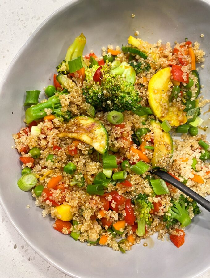 gray bowl with quinoa and colorful veggies and black fork
