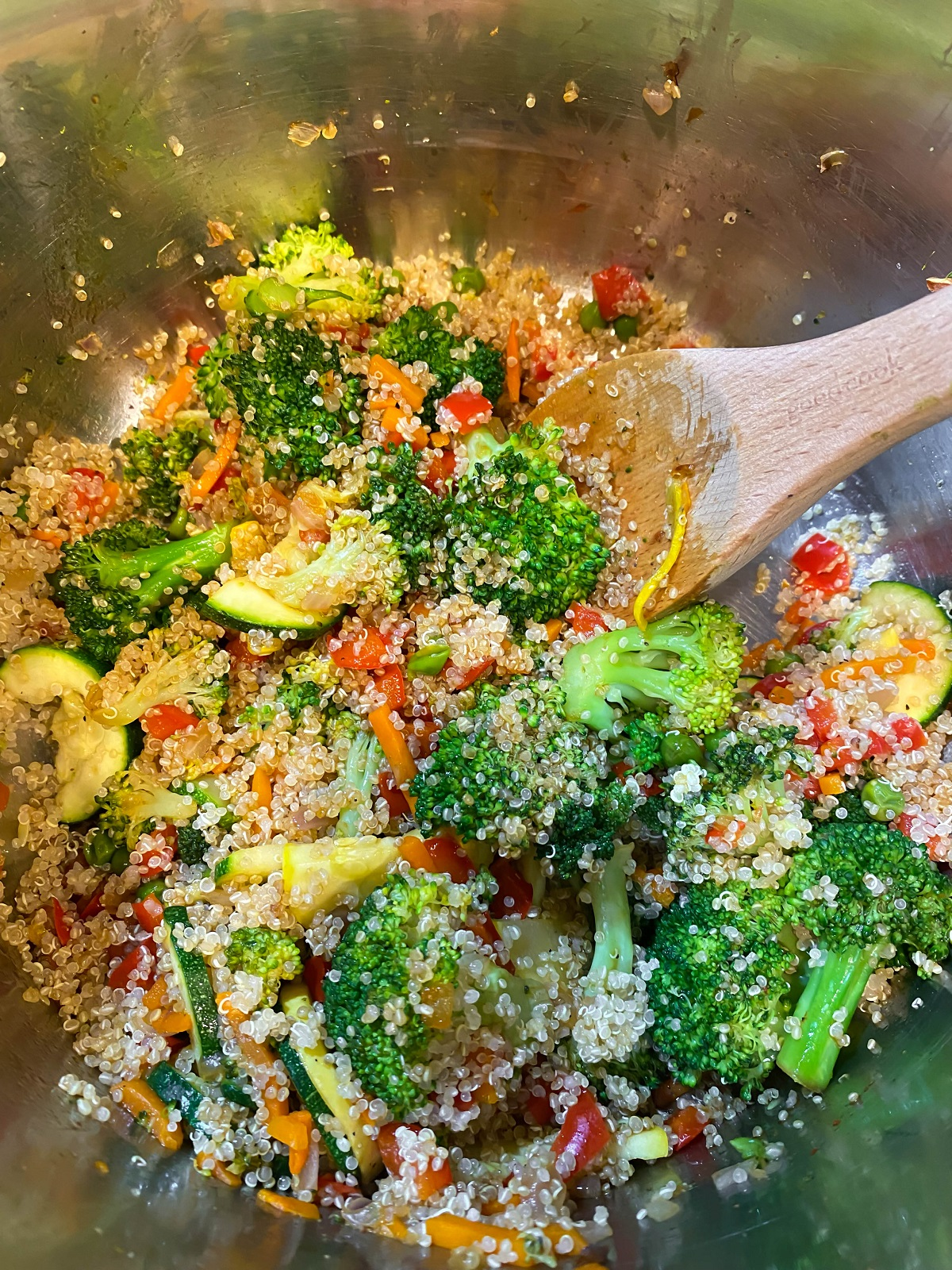 quinoa mixed with veggies and wooden spoon in large pot